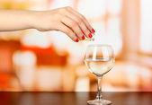 Algo verter en el vaso con la bebida en la mesa de madera en el fondo de la sala — Foto de Stock