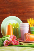 Multicolored plastic tableware on table with tulips on wooden background — Stock Photo