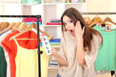 Young girl in shop buying clothes — Stock Photo