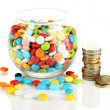 Colorful candies in glass bowl and coins isolated on white — Stock Photo