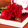 Wedding rings on bible with roses on wooden background — Stock Photo #22646371