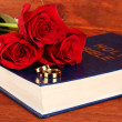 Wedding rings on bible with roses on wooden background — Stock Photo #22646421