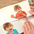 Photos in hands and photo album on wooden table — Stock Photo #22649785