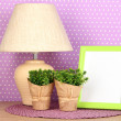 Colorful photo frame, lamp and flowers on wooden table on lilac polka dots background — Foto de Stock