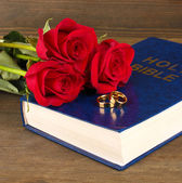 Wedding rings on bible with roses on wooden background — Zdjęcie stockowe