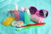 Hotel cosmetics kit on blue towel — Stock Photo