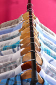 Men's shirts on hangers on pink background — Stock Photo