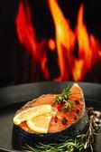 Fresh salmon steak on pan, on fire background, close up — Stock Photo
