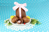 Composition of Easter and chocolate eggs on blue fabric background — Stock Photo
