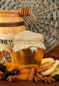 Jar of honey, wooden barrel, drizzler and dried fruits on wooden background — Stock Photo