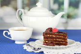 Teapot, cup of tea and delicious cake on window background — Foto de Stock