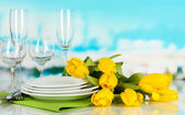 Yellow tulips and utensils for serving on blue natural background background — Stock Photo