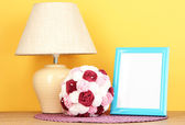 Colorful photo frame, lamp and flowers on wooden table on yellow background — Stock Photo