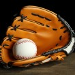 Baseball glove and ball on dark background - Stock Photo