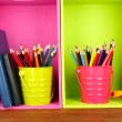 图库照片: Colorful pencils in pails on shelves with writing-pad on wooden background