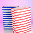 Stripped bags on light pink background — Stock Photo #22650677