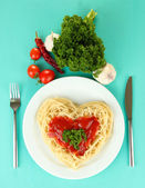 Cooked spaghetti carefully arranged in heart shape and topped with tomato sauce, on blue background — Stock Photo