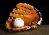 Baseball glove and ball on dark background — Stock Photo