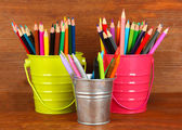 Colorful pencils in three pails on wooden background — Stock Photo