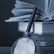 Magnifying glass over the stack of books in grey light on grey background — 图库照片