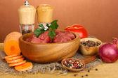 Surowy wołowiny marynowane z ziół i przypraw na drewnianym stole na brązowym tle — Zdjęcie stockowe