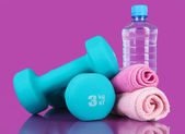 Dumbbells on purple background — Stock Photo