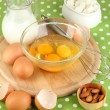 Stock Photo: Broken egg in bowl and various ingredients next to them on green tablecloth close-up