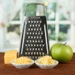 Metal grater and cheese, apple on bright background — Stock Photo