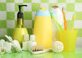 Bath accessories on shelf in bathroom on green tile wall background — Stock fotografie