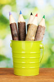 Colorful wooden pencils in pail on wooden table on bright background — Stock Photo