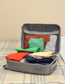 Open grey suitcase with clothing on bed — Stock Photo