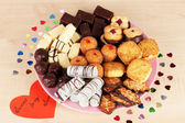 Sweet cookies with valentine card on plate on wooden background — Stock Photo