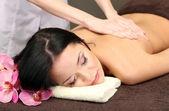Hermosa joven en el salón de spa recibiendo masaje con piedras del balneario, sobre fondo oscuro — Foto de Stock