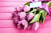 Vacker bukett lila tulpaner på rosa trä bakgrund — Stockfoto