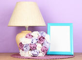 Colorful photo frame, lamp and flowers on wooden table on lilac background — Stock Photo