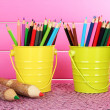 Colorful pencils in two pails on table on pink background — Stock Photo #22720227