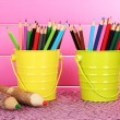 Colorful pencils in two pails on table on pink background — Stock Photo