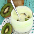 Delicious yogurt in glass with kiwi on wooden table close-up — Stock Photo #22720729