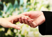 Priest holding woman hand, on green background — Stock Photo