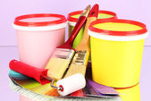 Set for painting: paint pots, brushes, paint-roller, palette of colors on lilac background — Stock Photo