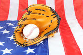 Baseball glove and ball on American flag background — Stock Photo