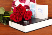 Wedding rings with roses on bible on wooden background — Stok fotoğraf