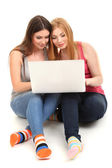 Two girl friends with with laptop isolated on white — Stock Photo