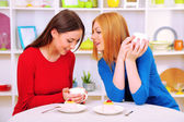 Two girl friends talk and drink tea in kitchen — Stock Photo