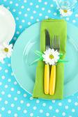 Coltello e forchetta, avvolto in un tovagliolo, su piastra, su colore sfondo tovaglia — Foto Stock