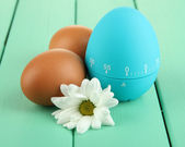 Blue egg timer and eggs, on color wooden background — Stock Photo