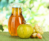 Apple juice in pitcher on table on bright background — Stock Photo