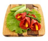 Involtini di salame con paprika pezzi all'interno, su tavola di legno, isolato su bianco — Foto Stock