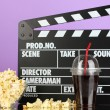 Movie clapperboard, coland popcorn on purple background — Stock Photo #22791562