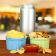 Snacks and beverage in metal can, on bright background — Stock Photo
